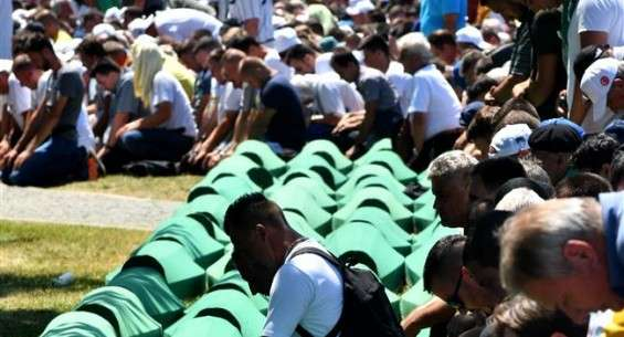 Bosnian Muslims, survivors of the 1995 Srebrenica massacre, as well as other visitors, pray near body caskets of their relatives, laid out at a memorial cemetery in the village of Potocari, near the eastern Bosnian town of Srebrenica, July 11, 2017. (Photo by AFP)