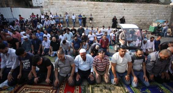 Palestinian worshippers perform the afternoon prayer outside the Al-Aqsa Mosque compound as they protest the detectors installed by Israel on 20 July 2017.